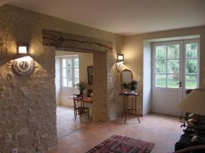 Pour donner l'accès à l'entrée, une percée a été faite dans le mur porteur qui a été décroûté pour faire apparaître la pierre.
